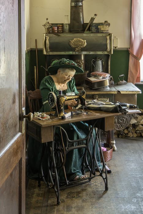 woman in period costume sitting at antique sewing table in mekiwin manor